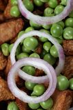 Onion rings and green peas Royalty Free Stock Images