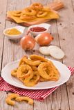 Onion rings. Onion rings with ketchup and mustard on white dish royalty free stock image
