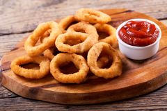 Onion rings with ketchup. On wooden board stock photography