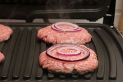 Rings lie on a piece of meat in the grill. Onion rings lie on a piece of meat in the grill Royalty Free Stock Photos
