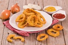 Onion rings. Onion rings with ketchup and mustard on white dish stock photography