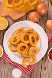 Onion rings. Onion rings with ketchup on white dish royalty free stock image