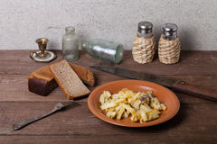 Onion, roasted potato, knive, salt, pepper and other things on t. He old wooden table Stock Images