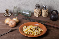 Onion, roasted potato, knive, salt, pepper and other things on t. He old wooden table Royalty Free Stock Photo
