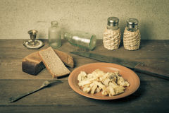 Onion, roasted potato, knive, salt, pepper and other things on t. He old wooden table. Toned Stock Photography