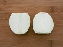 Onion sliced in half over cutting board Stock Images