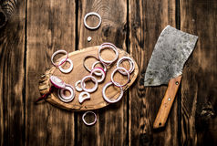 Onion sliced old hatchet. On wooden background. Stock Photography