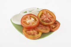 Onion slices and tomato slices. On neutral background Royalty Free Stock Photos