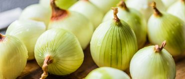 Onion and onion slices on wooden board. Onion and onion slices on wooden cutting board royalty free stock images