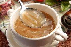 Onion soup. A close view of a soup spoon filled with onion soup royalty free stock image