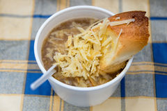 Onion soup with cheese and bread, street food in plastic ware. Royalty Free Stock Photography