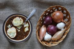 Onion soup with onions in basket. Onion Soup with blue stilton gruyere cheese with Garlic, French Echalion Shallots and red and brown onions in a wicker basket Royalty Free Stock Photos