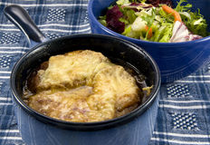Onion Soup and Salad on Blue Cloth. Bowl of French onion soup with bread and browned melted cheese floating on top.  Bowl is blue onion-soup crock with handle Royalty Free Stock Photos