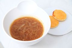 Onion soup in white bowl Stock Images