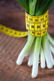 Onion stems and measurement tape Stock Image