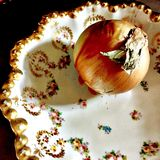 Onion still life in antique China bowl. A golden onion sets in a beautiful china bowl royalty free stock photography