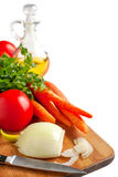 Onion, tomato, carrots and fresh parsley on a chopping board. Stock Images