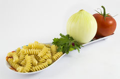 Onion, tomato, parsley and pasta. On white background Royalty Free Stock Photography