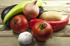 Onion, tomatoes, pepper, eggplant, garlic and pota. Toes on wooden place Royalty Free Stock Photos