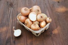 Onion on a wooden table in a basket Stock Photography