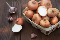Onion on a wooden table in a basket Royalty Free Stock Image