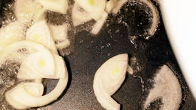 Onions being fried in a pan Stock Image