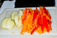 Onions Bell Peppers Sliced. Onions red and orange Bell Peppers prepped on a cutting board Royalty Free Stock Photo