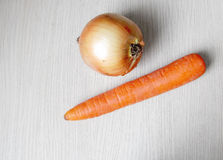 Onions and carrots on the table Royalty Free Stock Image