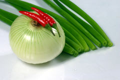 Onions and chili peppers. Spring and bulb onions and two chili peppers Royalty Free Stock Photography