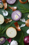 Onions, chives and garlic scattered on wood table Royalty Free Stock Photo