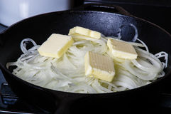 Onions cooking with butter in skillet Stock Images