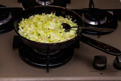 Golden onions fried in a pan royalty free stock photography