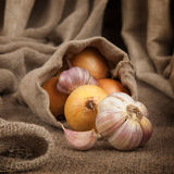 Onions and garlic in a bag of coarse cloth on the table Royalty Free Stock Image