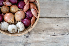 Onions and garlic in a basket on wooden background Stock Photos