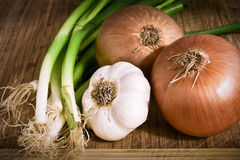 Onions, garlic on a chopping board Royalty Free Stock Photography