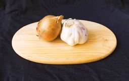 Onions and garlic on a chopping board. 