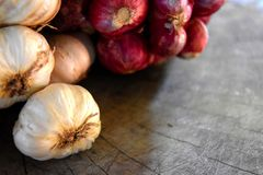 Onions and Garlic. On the wood dry on a wooden background and empty space for text Stock Photo