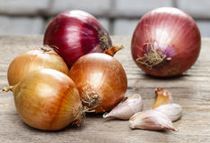 Onions and garlic on wooden table Stock Photo