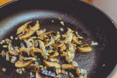 Onions and mushrooms frying in pan Stock Photography