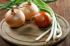 Onions napiform and green on an  rural table Royalty Free Stock Photography