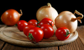 Onions napiform tomatoes on an  rural table Royalty Free Stock Photos
