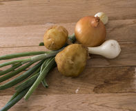 Onions and new potato. Image of onions and new potato on wood background Stock Photo