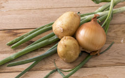 Onions and new potato. Image of onions and new potato on wood background Royalty Free Stock Photo