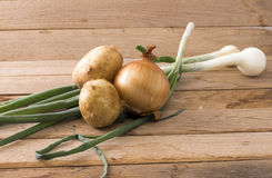 Onions and new potato. Image of onions and new potato on wood background Royalty Free Stock Image