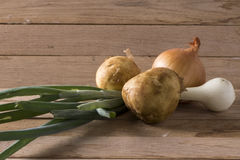 Onions and new potato. Image of onions and new potato on wood background Royalty Free Stock Photos