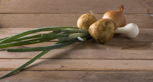 Onions and new potato. Image of onions and new potato on wood background Royalty Free Stock Images