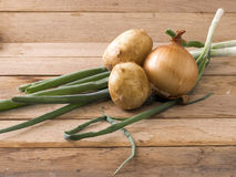 Onions and new potato. Image of onions and new potato on wood background Stock Photos