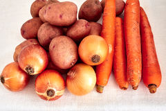 Onions, potatoes, carrots. Raw onions, potatoes, carrots on a white tablecloth Royalty Free Stock Photography