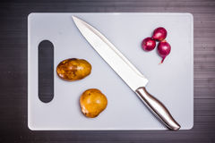 Onions, potatoes and knife on cutting board Stock Photo