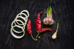 Onions, red pepper and garlic on a dark table Stock Images